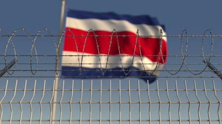 Defocused waving flag of Costa rica behind barbed wire fence. 3D rendering 免版税图像