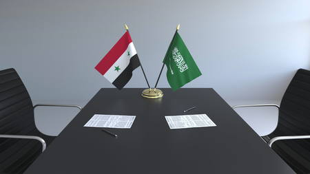 Flags of Syria and Saudi Arabia and papers on the table. Negotiations and signing an international agreement. Conceptual 3D rendering