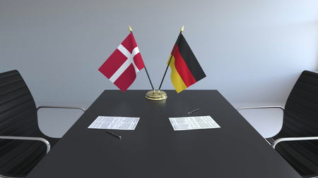 Flags of Denmark and Germany and papers on the table. Negotiations and signing an international agreement. Conceptual 3D rendering