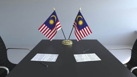 Flags of Malaysia and papers on the table. Negotiations and signing an agreement. Conceptual 3D rendering Imagens