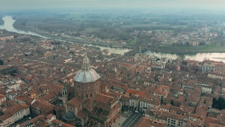 Aerial shot of Duomo di Pavia cathedral and the Ponte Coperto Bridge within the cityscape of Pavia, Italy 免版税图像