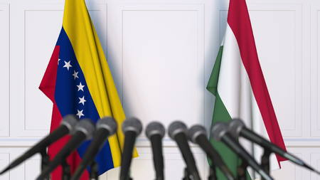 Flags of Venezuela and Hungary at international meeting or negotiations press conference. 3D rendering