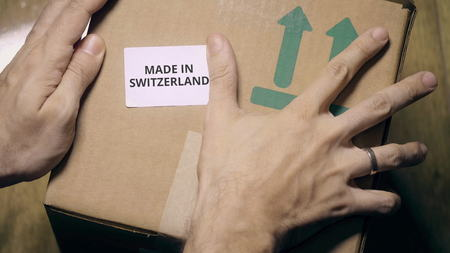 Labeling carton with MADE IN SWITZERLAND sticker