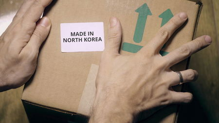 Placing sticker with MADE IN NORTH KOREA text on the box