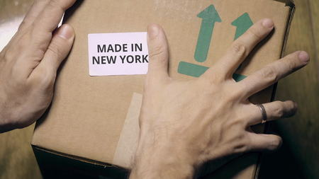 Placing sticker with MADE IN NEW YORK text on the box
