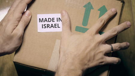 Placing sticker with MADE IN ISRAEL text on the box Stock fotó - 120238734