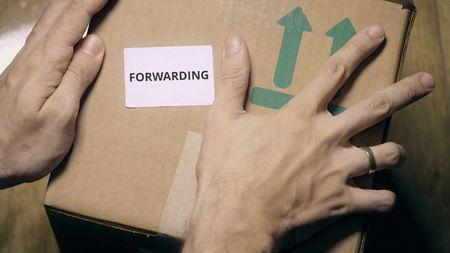 Placing FORWARDING sticker on a carton