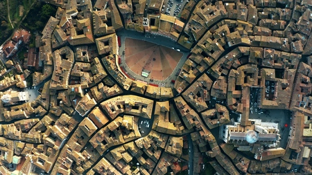Aerial top-down view of Siena involving Piazza del Campo or Campo Square, a place of famous horse-race, Palio di Siena. Italy