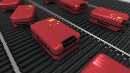Suitcases featuring flag of China move on the conveyor in an airport. Chinese tourism related 3D rendering