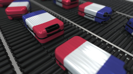 Suitcases featuring flag of France move on the conveyor in an airport. French tourism related 3D rendering