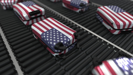 Suitcases featuring flag of the USA move on the conveyor in an airport. American tourism related 3D rendering