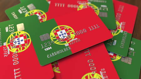 Pile of credit cards with flag of Portugal. Portuguese banking system conceptual 3D rendering