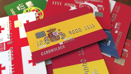 Many credit cards with different flags, emphasized bank card with flag of Spain. 3D rendering