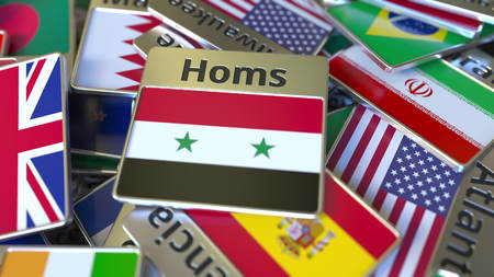 Souvenir magnet or badge with Homs text and national flag among different ones. Traveling to Syria conceptual 3D rendering