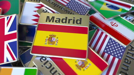 Souvenir magnet or badge with Madrid text and national flag among different ones. Traveling to Spain conceptual 3D rendering Stockfoto