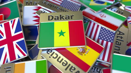 Souvenir magnet or badge with Dakar text and national flag among different ones. Traveling to Senegal conceptual 3D rendering Фото со стока