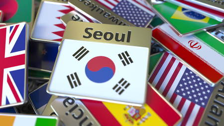 Souvenir magnet or badge with Seoul text and national flag among different ones. Traveling to South Korea conceptual 3D rendering Фото со стока
