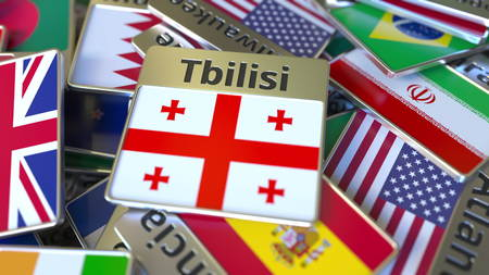 Souvenir magnet or badge with Tbilisi text and national flag among different ones. Traveling to Georgia conceptual 3D rendering Stockfoto