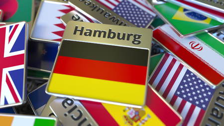 Souvenir magnet or badge with Hamburg text and national flag among different ones. Traveling to Germany conceptual 3D rendering