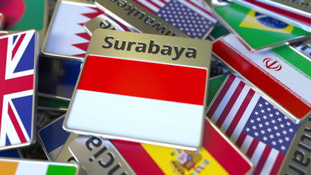 Souvenir magnet or badge with Surabaya text and national flag among different ones. Traveling to Indonesia conceptual 3D rendering Stockfoto
