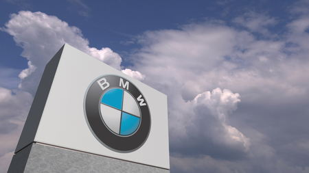 Logo of BMW on a stand against cloudy sky, editorial 3D rendering Editorial