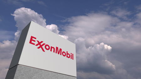 Logo of EXXON MOBIL on a stand against cloudy sky, editorial 3D rendering