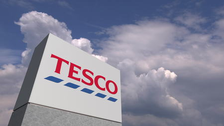 Logo of TESCO on a stand against cloudy sky, editorial 3D rendering