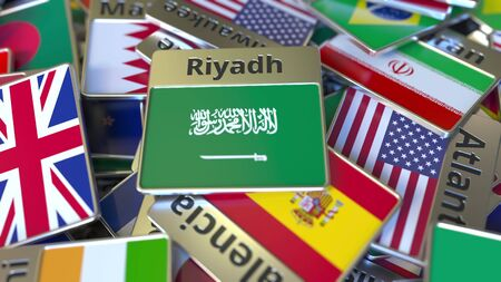 Souvenir magnet or badge with Riyadh text and national flag among different ones. Traveling to Saudi Arabia conceptual 3D rendering Фото со стока