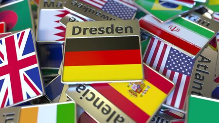 Souvenir magnet or badge with Dresden text and national flag among different ones. Traveling to Germany conceptual 3D rendering Фото со стока