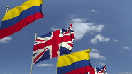Flags of Colombia and the United Kingdom against blue sky, 3D rendering