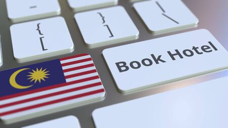 BOOK HOTEL text and flag of Malaysia on the buttons on the computer keyboard. Travel related conceptual 3D rendering Фото со стока