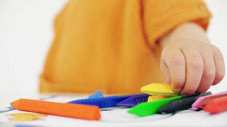 Blonde baby girl putting yellow crayon on the table Imagens