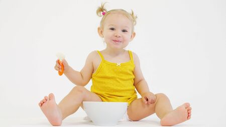 Happy blonde baby girl eats her oatmeal against white background