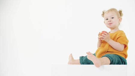 Baby wearing orange and green clothes eats apple against white background