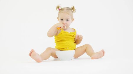 Funny baby girl eats her meal with a spoon