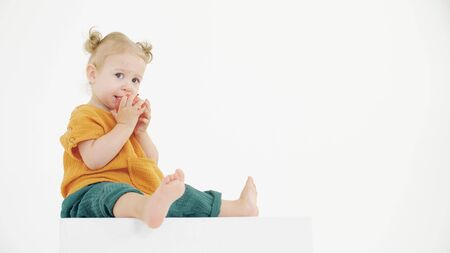 Pensive baby wearing orange and green clothes eating apple on white background