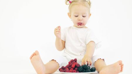 Baby girl eating fresh berries on white background Standard-Bild - 129042982