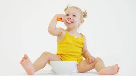Smiling baby girl eating her breakfast on white background Standard-Bild - 129042979