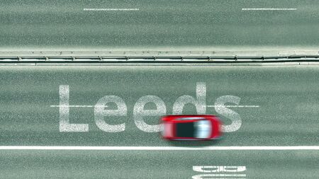 Aerial top down view of the road with cars revealing Leeds caption. Car travel to the United Kingdom 3D rendering