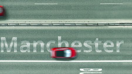Aerial down view of the motorway with cars revealing Manchester caption. Car travel to the United Kingdom 3D rendering