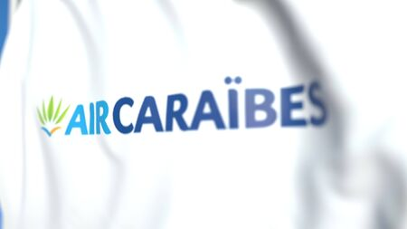 Flying flag with Air Caraibes logo, close-up. Editorial 3D rendering