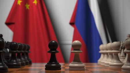 Flags of China and Russia behind chess board. The first pawn moves in the beginning of the game. Political rivalry conceptual 3D rendering