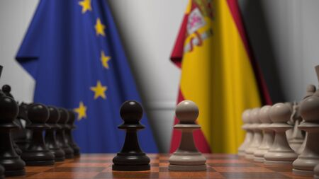Flags of the EU and Spain behind chess board. The first pawn moves in the beginning of the game. Political rivalry conceptual 3D rendering