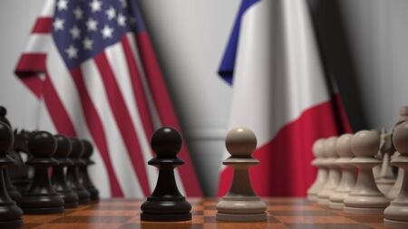 Flags of United States and France behind chess board. The first pawn moves in the beginning of the game. Political rivalry conceptual 3D rendering Stockfoto