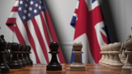 Flags of United States and United Kingdom behind chess board. The first pawn moves in the beginning of the game. Political rivalry conceptual 3D rendering