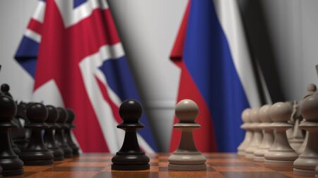 Flags of the UK and Russia behind chess board. The first pawn moves in the beginning of the game. Political rivalry conceptual 3D rendering
