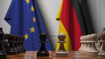 Flags of the EU and Germany behind chess board. The first pawn moves in the beginning of the game. Political rivalry conceptual 3D rendering