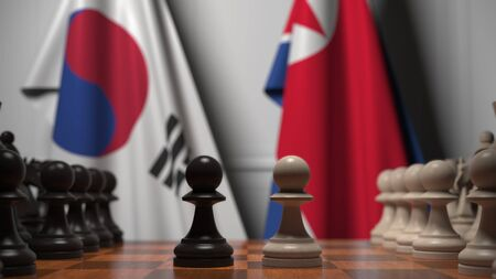 Flags of South Korea and North Korea behind chess board. The first pawn moves in the beginning of the game. Political rivalry conceptual 3D rendering