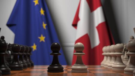 Flags of the EU and Switzerland behind chess board. The first pawn moves in the beginning of the game. Political rivalry conceptual 3D rendering