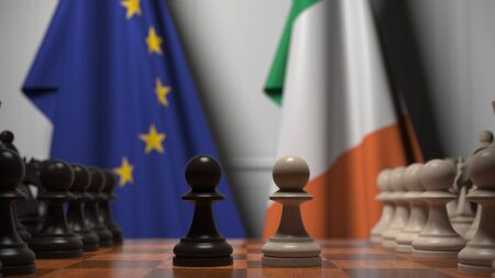 Flags of the EU and the Republic of Ireland behind chess board. The first pawn moves in the beginning of the game. Political rivalry conceptual 3D rendering